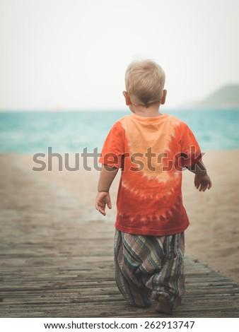 Baby walking along the beach - stock photo