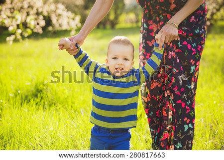 baby walking in green park holding hands of mother. happy little child playing outside with parents. first steps of infant. beautiful boy in spring blooming garden having fun with mom. - stock photo