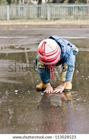 Baby washes up on the road in a muddy puddle. - stock photo