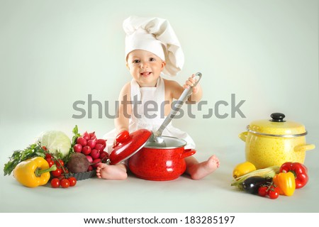 Baby wearing a chef hat with vegetables and pan. Use it for child, healthy food concept - stock photo