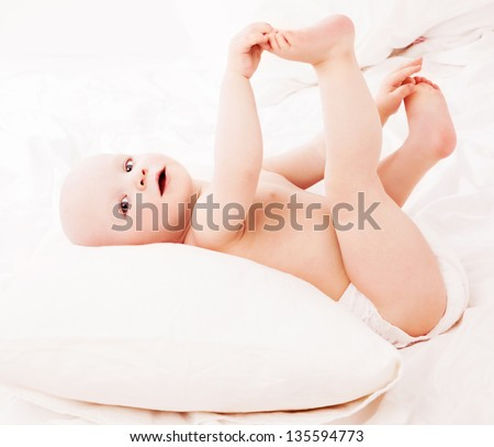 baby wearing diapers in bed at home - stock photo