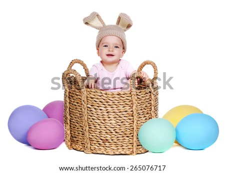 baby wearing  rabbit hat sitting in a basket with giant easter eggs - stock photo