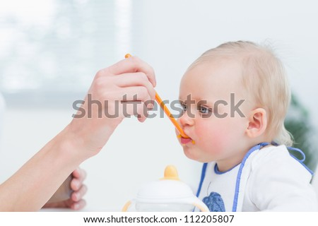 Baby with a plastic spoon on his mouth in living room - stock photo