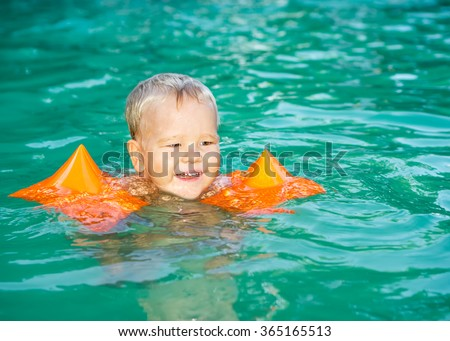 Baby with armbands in swimming pool - stock photo