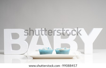 baby with cupcakes on a plate - stock photo