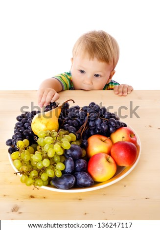 Baby with dish of fruit on the table, isolated on white - stock photo