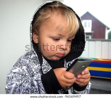 Baby with mobil telephone - stock photo