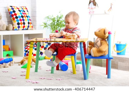 Baby with puzzle at the table in playing room - stock photo