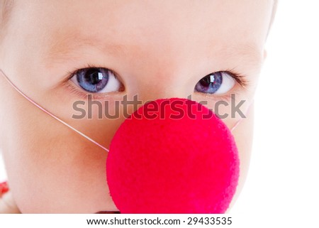 Baby with red clown nose on, shot closeup - stock photo