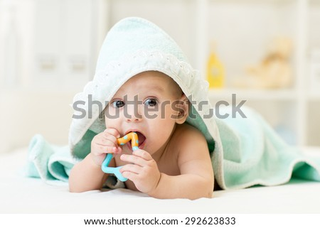 baby with teether in mouth under bathing towel at nursery - stock photo