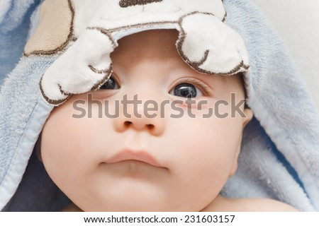 baby wrapped in a towel after a swim - stock photo