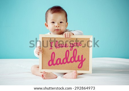 """Baby writing """"I Love you Daddy"""" on the board, new family concept, studio shot - stock photo"""