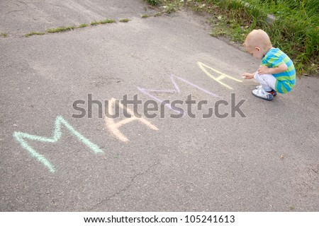 "Baby writing the word ""mother"" colorful chalk on the pavement - stock photo"