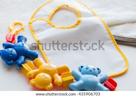 babyhood, childhood, accessory and object concept - close up of baby rattle and bib for newborn boy on towel - stock photo