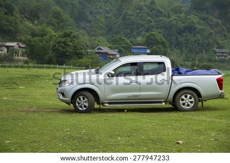Bac Kan, Viet Nam - Apr 24, 2015: Nissan NP300 Navara car crossing glass fields in Babe lake in Vietnam - stock photo