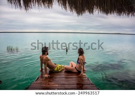 Bacalar Lake at Riviera MAya, Quinatana Roo. Couple sitting on a dock contemplating. Water motion. - stock photo