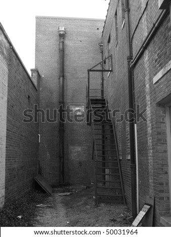 back alley shown in black and white - stock photo