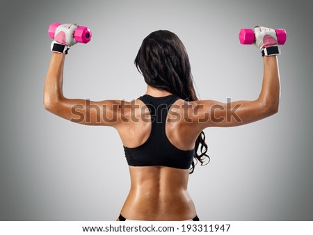 back and hands of a young sporty muscular woman working out with two dumbbells - stock photo