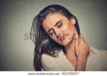 Back and spine disease. Closeup portrait tired woman massaging her painful neck isolated on gray wall background. Face expression  - stock photo