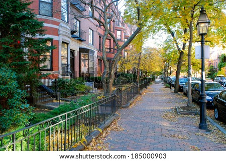 Back Bay Boston in the Fall - Red brick sidewalk and brownstones, iron fence and street lamps - stock photo