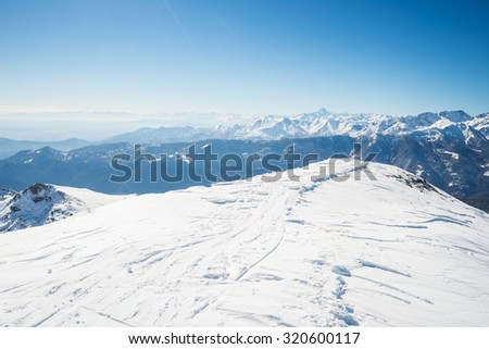 Back country ski tracks on snowcapped ridge and summit with majestic view of the alpine arc in a winter scenery. Clear blue sky. Piedmont, italian Alps. - stock photo