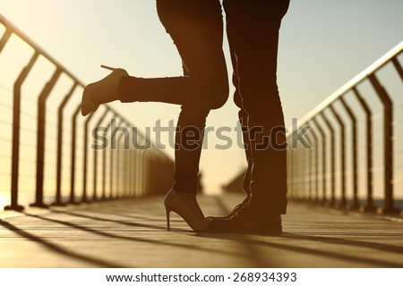 Back light of a couple legs silhouette hugging with love in a bridge at sunset - stock photo