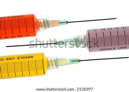 Back lighted image of a syringe containing colorful liquids for a high key effect. - stock photo