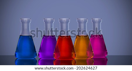 Back lit laboratory flasks in different colors - stock photo