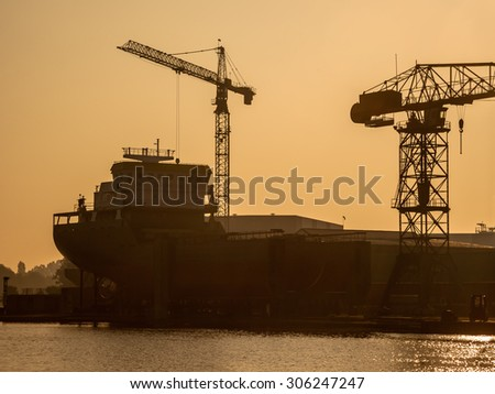 Back lit Silhouette of a Ship Being Constructed on a Wharf in the Netherlands - stock photo
