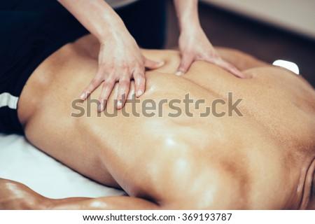 Back massage. Massage therapist massaging lower back region of a male athlete. Toned image - stock photo