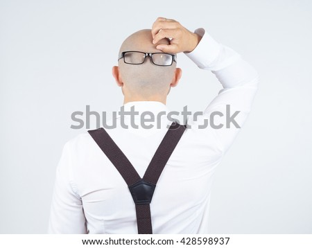 back of a bald-headed man in a white shirt with glasses on nape. scratches his head  - stock photo