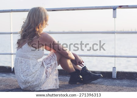 Back of a blond woman wearing white lace dress and short black boots looking to the lake enjoying sun. Fashion for young people. - stock photo