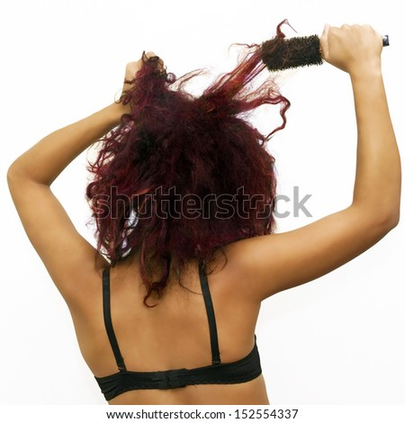 Back of a Female Trying to Brush Wild Dyed Hair - stock photo