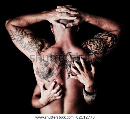 Back of a Man with tattoos with a woman's hands scratching his back - stock photo