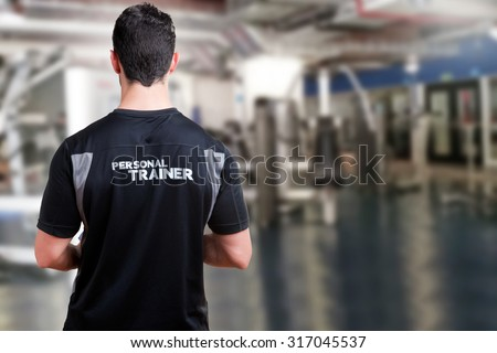 Back of a Personal Trainer in a gym - stock photo
