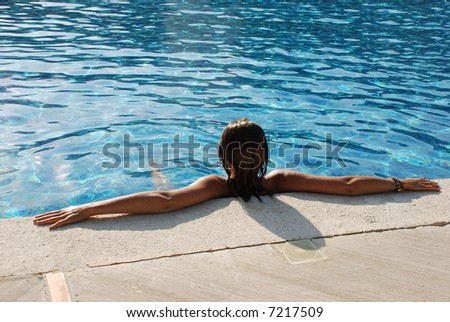 Back of a woman in a pool or jacuzzi at a resort - stock photo