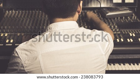 back of asian sound engineer work on recording studio mixer & piano, keyboard, synthesizer / old film processed - stock photo