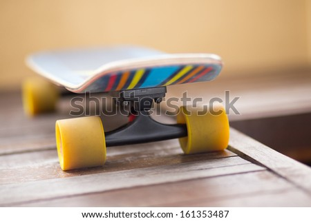 Back of colorful cruiser skate board with yellow wheels in perspective view - stock photo