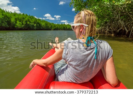 Back of fashionable woman tourist with braids on a red kayak in the famous mangroves of Ao Phang Nga Bay National Park, Krabi, Thailand. - stock photo