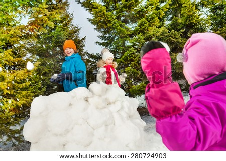 Back of girl throw snowball while playing game - stock photo