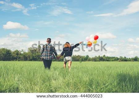 Back of happy young asian couple holding balloon and walk together on green grass. - stock photo