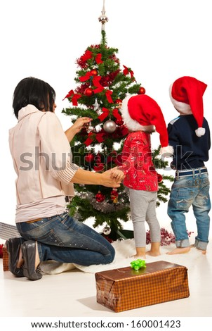 Back of mother with two kids decorate Christmas tree  - stock photo