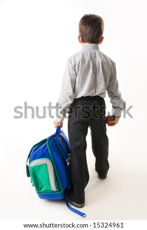 Back of schoolboy holding backpack and apple while going to school - stock photo