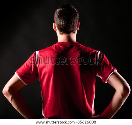 back of soccer player on black background - stock photo