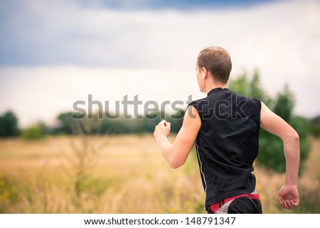 Back of sportive man runner jogging at great speed on a road - stock photo