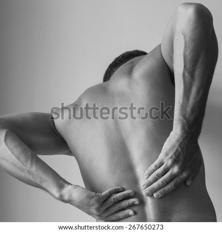 Back of Strong young Caucasian man with hands, black and white studio photo - stock photo