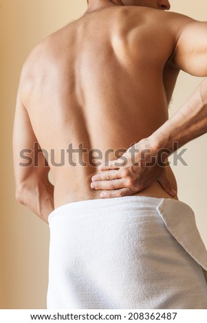Back of Strong young Caucasian man with white towel - stock photo
