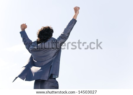 Back of successful businessman in suit raising his hands - stock photo