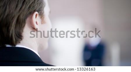 back of the head of a businessman looking at another businessman - stock photo