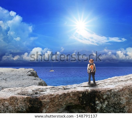 back of young man standing on rock cliff and looking to sea - stock photo